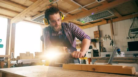 skillful : Slow motion of a male carpenter using a jigsaw to cut the wood Stock Footage