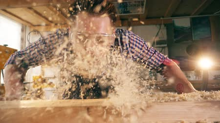 стружки : Wood shavings are getting blown off by the craftsman in slow motion Стоковые видеозаписи