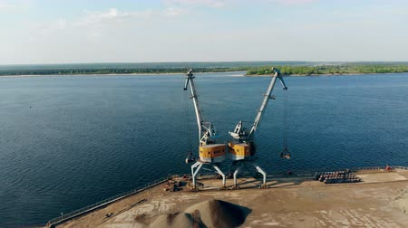 dois objetos : Two cranes unloading a barge full of breakstones at docks.