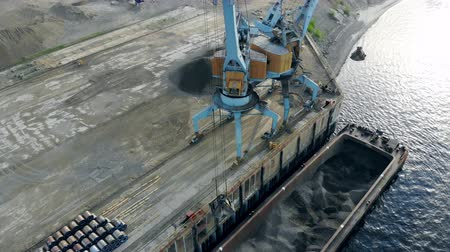 ezilmiş : Process of unloading a barge with rubble with two cranes.