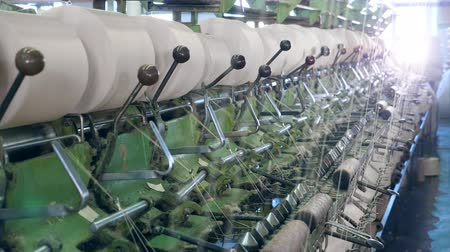 poliester : Metal machines work with threads at a textile factory, coiling them onto bobbins. Archivo de Video