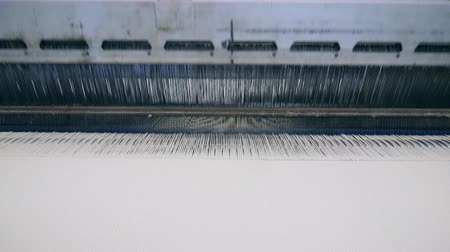 závit : Textile plant machine weaves white fabric automatically. Textile factory equipment in work.