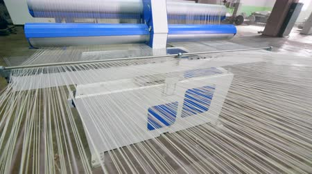 編まれた : White fabric woven on a special loom at a textile factory.