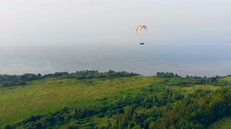 glides : Man paragliding over green field. Stock Footage