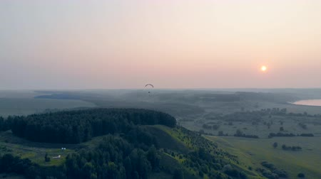 padák : Man floats with a glider on a sunset background in sky. Paragliding, action, extreme sport concept.