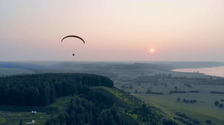parachuting : A sportsman flies with a glider on a sunset background. Paragliding, action, extreme sport concept. Stock Footage
