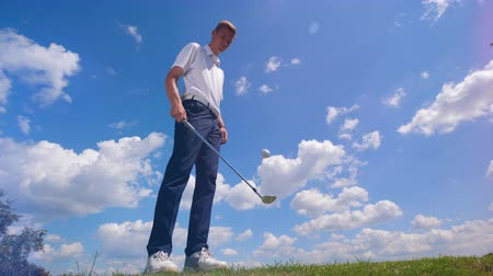 t şeklinde : A man juggles golfing ball with a golf club.