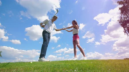 golfjátékos : One man teaches a girl to play golf at a golf course.