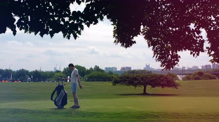 çimenli yol : One golfer takes a club from a bag on a course.