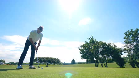 golfjátékos : A golfer hits a ball, putting it into a hole.