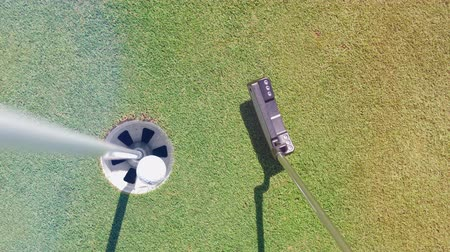 çimenli yol : White ball getting into a hole on a golf field.
