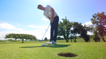 kap : Man gets a ball into a hole, while playing golf. Stock mozgókép