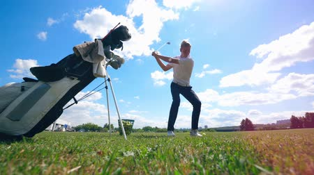 çimenli yol : A man practices on a golf field, hitting a ball.