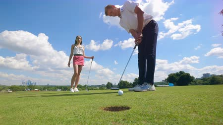 инструктор : Golf player puts a ball into a hole at a golf course while woman is watching.