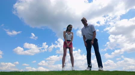 çimenli yol : Man and woman training, playing golf at a course. Stok Video