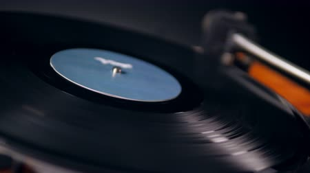 gramophone : Rotating vinyl record and the cartridge being removed from it