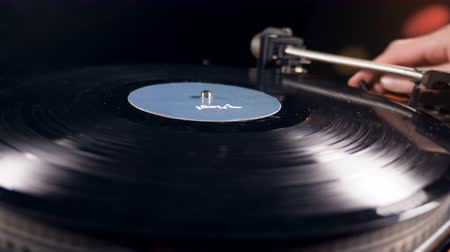 detalhado : A person is putting a vinyl record onto the player