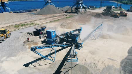 explotacion : Crushed stones moving on a conveyor at extraction site. Mining industry equipment.