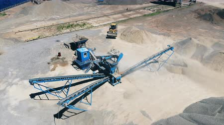 verhuizer : Yellow tractor works on a mining site, moving rubble. Rock stone crushing machine at a mining quarry.