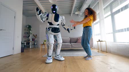 droid : Young woman and the cyborg are doing a robot dance. Robot, human-like cyborg concept.