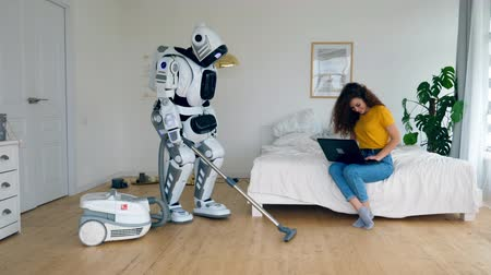 droid : A lady is sitting with a laptop and a robot is cleaning
