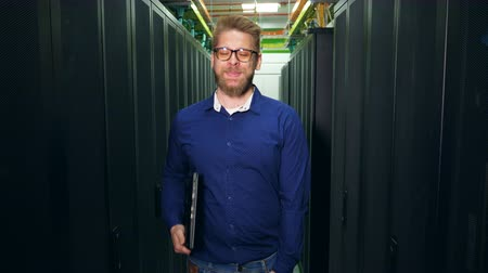 beheerder : IT specialist in glasses is smiling at camera