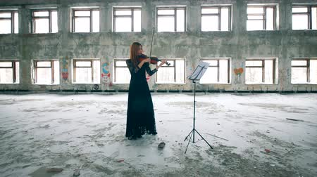 yıkık : Rundown building with a woman playing the violin in it