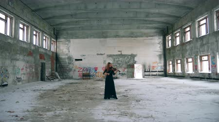 просторный : Abandoned building and a woman playing the violin in it