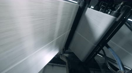 nakladatelství : Rolling conveyor moves newspaper sheets in printing office.