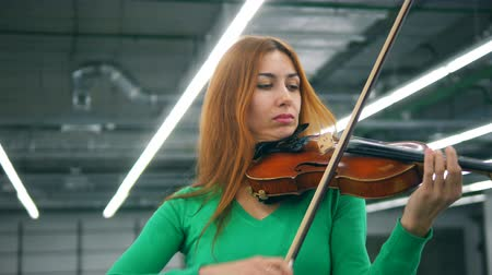 concert hall : Gorgeous lady is playing the violin professionally