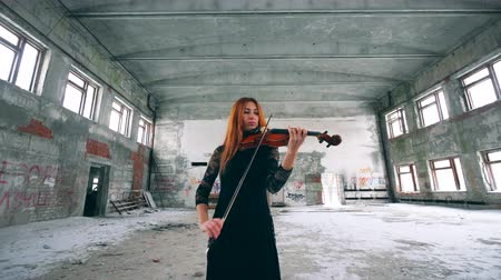 просторный : Redhead lady is playing the violin in an abandoned building