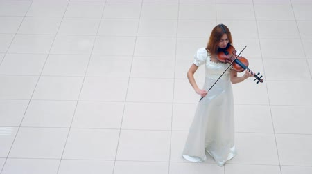 cellist : Top view of a lady in white dress playing the musical instrument