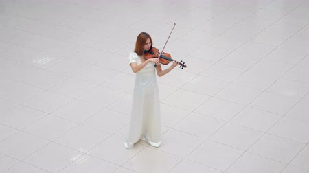 cellist : Woman in white dress is playing the violin while standing on white tile