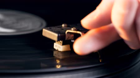 stereoanlage : Man puts a music player needle onto a vinyl disk. Videos