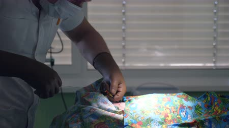 intensive care unit : A doctor performs surgery on a newborn baby in a hospital room. Stock Footage