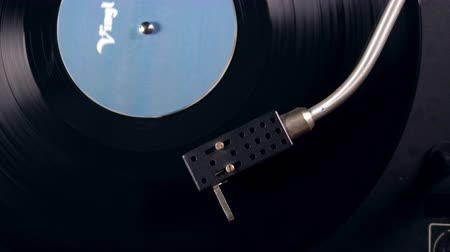 jogador : Metal needle scratches vinyl record while a music player works.