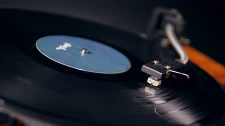 stereoanlage : One person puts a metal needle of a vinyl player onto a record.