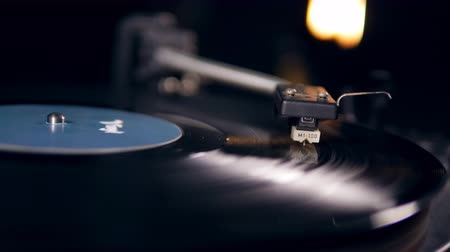 vinil : Black vinyl record rotates on a vintage player with a needle.