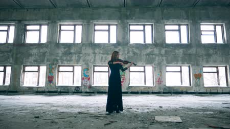 hegedűművész : Female violinist is playing the instrument in a rundown hall