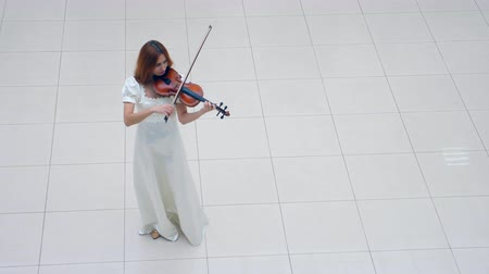concert hall : White floor with a lady standing on it and playing the violin
