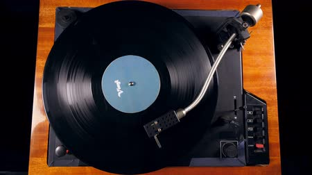 gramophone : Black platter rotates on a vinyl player with needle.