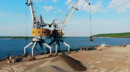 fosilní : Crushed stones unloaded at docks with two cranes.