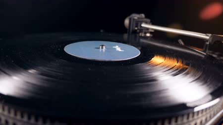 akusztikus : Person puts a vinyl record on a player and turns it on.