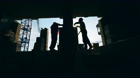 alvenaria : Backlit construction workers are building a wall Stock Footage