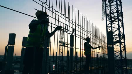 kader : Construction workers are making a metal framework at sunset Stockvideo