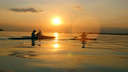 canoe kayak : Paddlers are canoeing while the sun is setting at the lake
