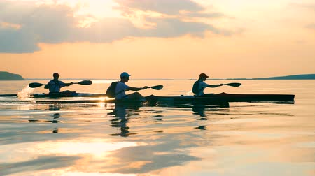 каноэ : Sunset waterscape with people canoeing Стоковые видеозаписи