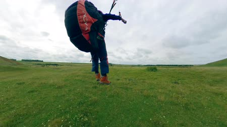 glide : Sportsperson flying a paraglider, lands on a field.