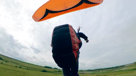 szybowiec : A man lands on a field after flying with a paraglider.