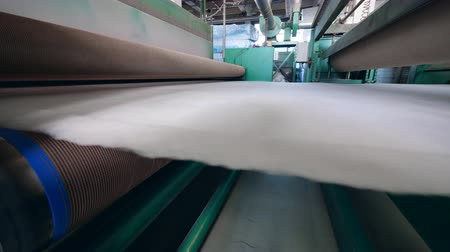 poliester : Synthetic fiber moving on a factory line with rollers.